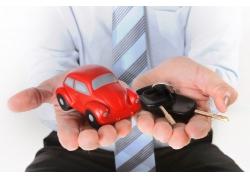 双手捧着汽车模型与钥匙的人物