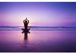 海滩练瑜伽的女性