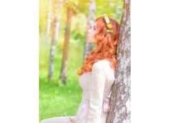 背靠着树木的性感美女
