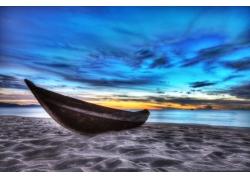 蓝天下沙滩上的小舟图片