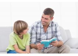 坐在沙发看书的父子俩