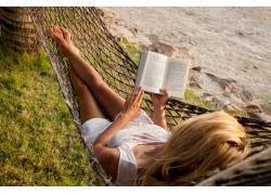 躺在吊床看书的美女图片