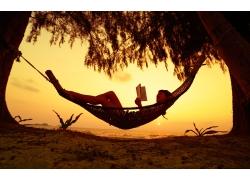 沙滩吊床看书的美女图片
