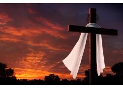 红色天空下的十字架和白布