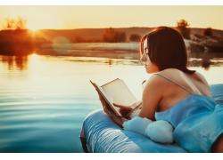 趴在浮床上看书的美女图片