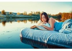 趴在浮床看书的性感美女图片