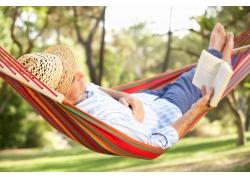 在吊床上看书的男人图片