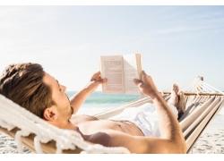 海边吊床上看书的男人图片