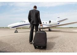 拉着行李箱的男人和飞机