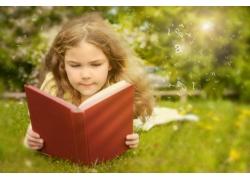 趴在草地上看书的小女孩图片