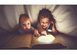 用手电筒看书的女孩和婴儿图片
