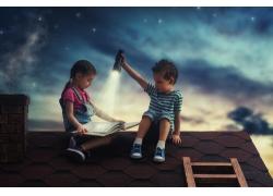 屋顶拿着手电筒看书的孩子图片
