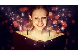 看着魔法书微笑的女孩图片