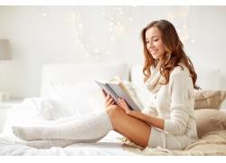 坐在床上看书的美女图片