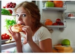 冰箱前吃面包的美女