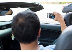坐在汽车里拍照的男人