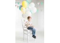 坐在椅子上吃蛋糕的男孩