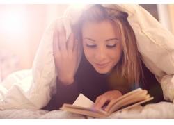 趴在被窝里看书的女孩图片