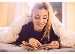 趴在被窝里看书的美女图片