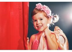 手扶红色窗帘的小女孩图片
