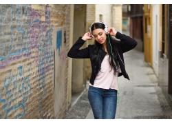 小巷里戴耳机的女人