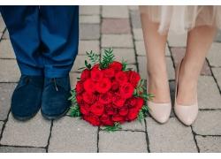 地上的玫瑰花束和新人的双脚