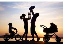 夕阳下海边的家庭图片