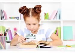 用放大镜看书的女孩图片