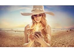 戴帽子玩手机的美女